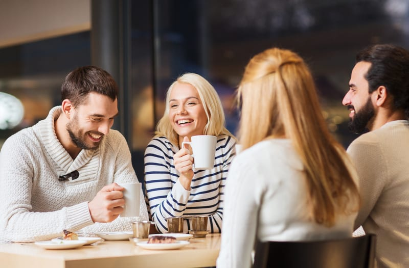 Group of friends talking and enjoying coffee and cake in a cafe